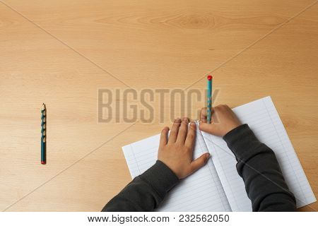 Child Writes On A Notebook.  Over Top View.