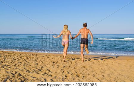 The young couple runs to plunge into the sea. Zacharo beach, Greece. poster