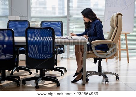 Profile View Of Pretty Young Entrepreneur Sitting At Table And Taking Necessary Notes While Preparin