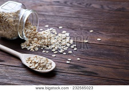 Overturned Glass Jar And Wooden Spoon With Raw Oatmeal On Vintage Wooden Background, Close-up, Top V