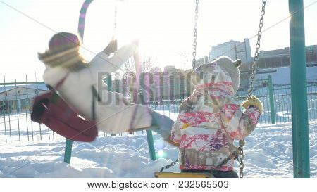 Young Mother With Child Swinging On Swing Set Outdoor In Winter Park. Snow Falling, Snowfall , Winte
