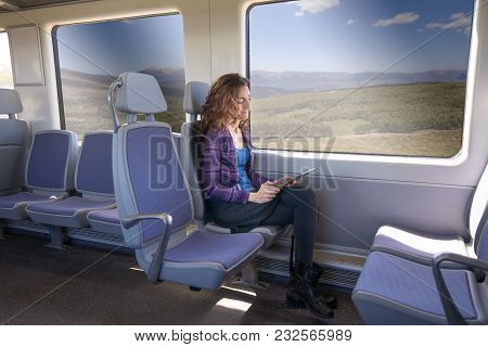 Side View Of Woman In Train Reading Digital Tablet