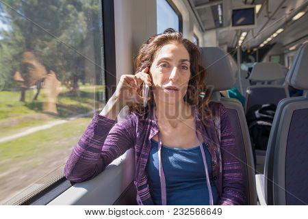Woman In Train Talking On Mobile