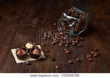 Side View Of Overturned Transparent Glass Jar With Roasted Coffee Beans And Sweet Chocolate Candies