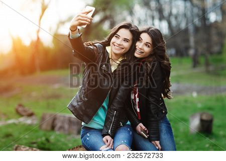 Two Pretty And Happy Young Woman Using Mobile Phone In The Park. Best Friends Make Selfie