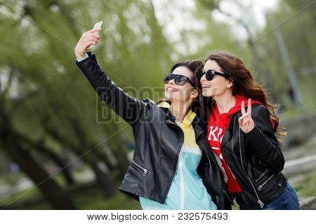 Two Pretty And Happy Young Woman Taiking Selfie With Mobile Phone In The Park. Best Friends Concept