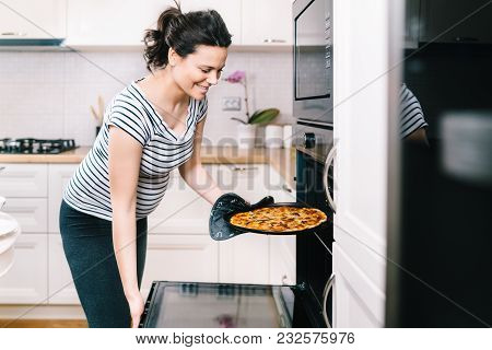Beautiful Pregnant Woman In Home Kitchen Preparing Pizza And Baking