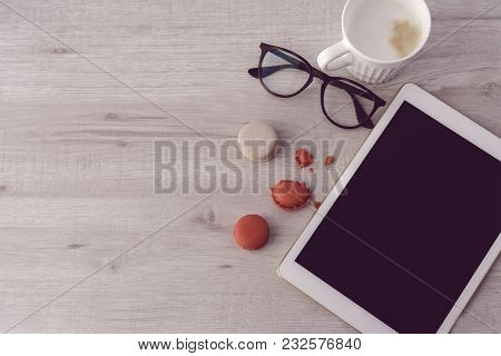 Colorful Macaroons, Glasses, Tablet With Blank Screen And A Cup Of Coffee On The White Wooden Backgr
