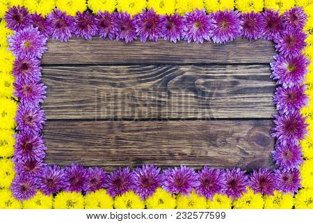Flower Frame. Frame Of Yellow And Blue Chrysanthemum Flowers On A Brown Wooden Background With A Pla