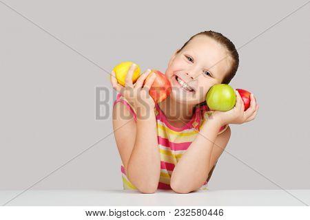 Cheerful little girl with fruit posing in studio