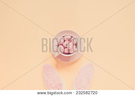 Easter Holiday Background With Bunny Ears And Easter Eggs In Coffee Cup. Copy Space Background. Flat