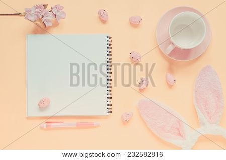 Easter Holiday Background With Notebook And Pen, Cup For Coffee, Bunny Ears And Easter Eggs. Copy Sp