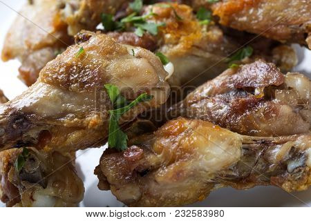 Close Up Of Fresh Grilled Chicken Drumsticks With Parsley Leaves On White Plate