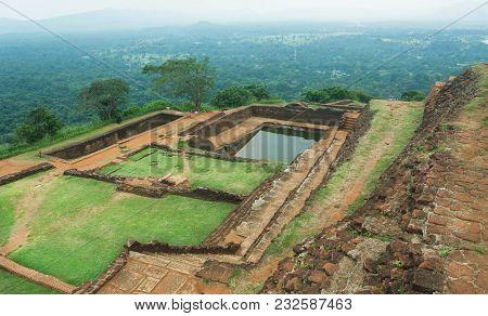 Green Plateau Of Mountain City Sigiriya With Rural Landscape, Water Pool, Ruins And Trees, Sri Lanka