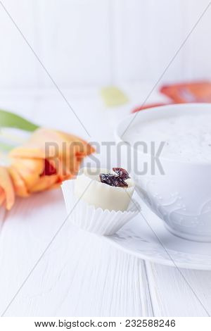 Coffee Cappuccino In A White Cup, White Chokolate Candy And Orange Tulips On A White Wooden Backgrou