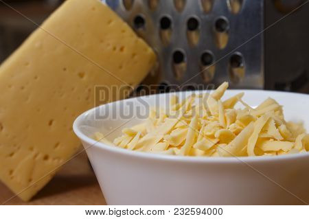 Grated Dutch Cheese In A Plate On A Wooden Board