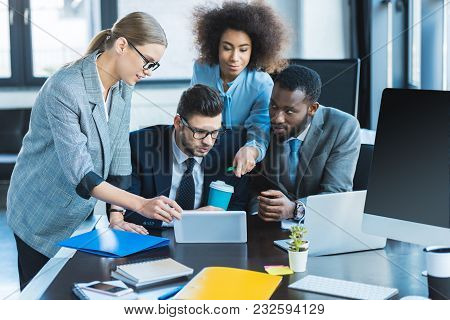 Multiethnic Businesspeople Looking At Tablet In Office