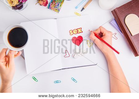 Woman Planing Date And Sex In Her Personal Organizer. Hands With Pencil And Coffee Cup Under Noteboo