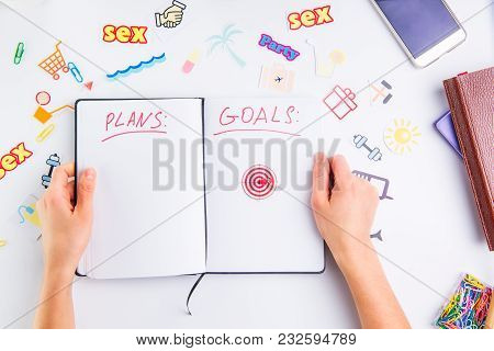 Female Hands Holding Personal Organizer With Plans And Goals Headline And Pushpin As Arrow On Target