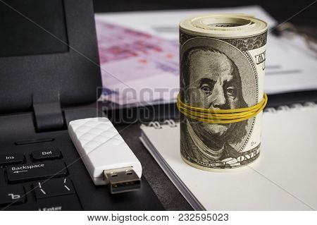 A Lot Of Dollars On A Notebook Near A Laptop With A Flash Drive