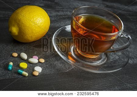 A Pile Of Pills With A Cup Of Tea And Lemon