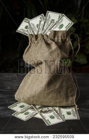 A Full Bag Of Dollars On A Dark Table