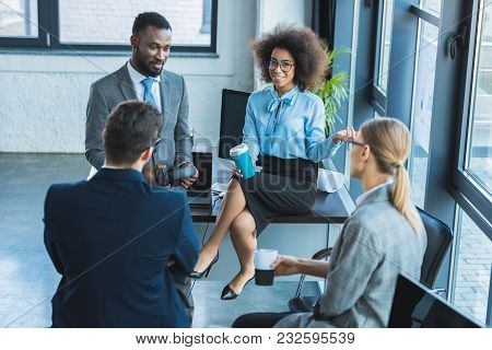 High Angle View Of Multicultural Businesspeople Having Coffee Break In Office