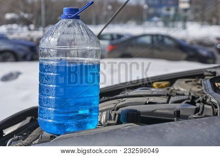 Bottle With Non-freezing Liquid For Windshield Washer Standing On The Engine Of A Car In Front Of A