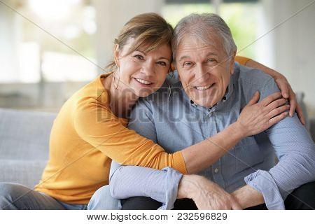 Portrait of senior couple at home sitting on sofa