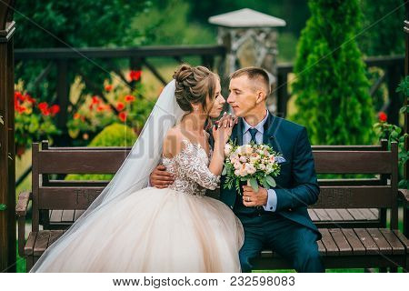 Happy Bride And Groom Standing On Wedding Ceremony Under The Arch Decorated With Flowers And Greener
