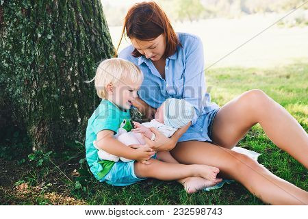 Mother With Little Baby Daughter And Older Son On Walking Outdoor. Woman Holding Newborn Baby With O