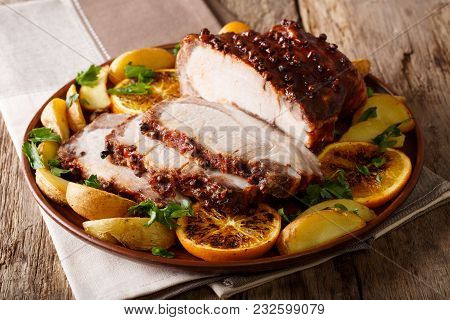 Roasted Christmas Ham With Orange Slices And Vegetables  Close-up On A Plate. Horizontal