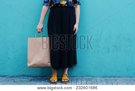 Close-up Of Young Girl With Shopping Bag On A Street With Blue Wall In Background.