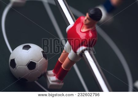 Horizontal Closeup With Selective Focus Of Red Shirt Player Figurine With Ball At His Feet On Foosba