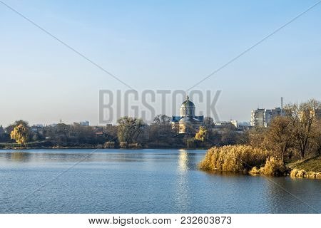 Wide River On A Sunny Autumn Day. Multi-storey Buildings And Church Across The River. Cityscapes And