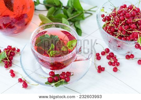Redcurrant Drink In Transparent Glass Carafe And Cup. Clear Glass Vase With Red Currant Berries On T