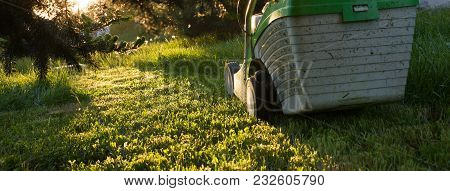Mowing The Grass. Lawn Mower On Green Lawn