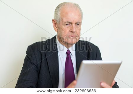 Closeup Portrait Of Focused Senior Business Man Reading News On Tablet Computer. Technology In Busin