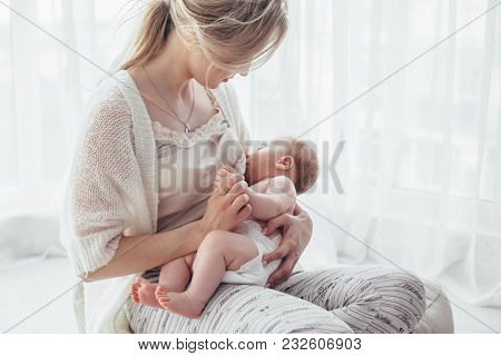 Bright portrait of a mom breast feeding baby over window lighting.