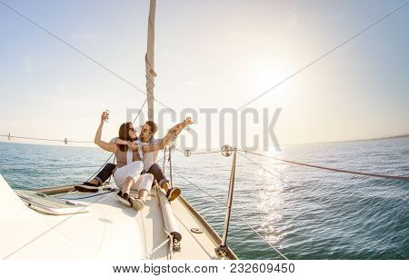Young Couple In Love On Sail Boat With Champagne At Sunset - Happy People Lifestyle On Exclusive Lux