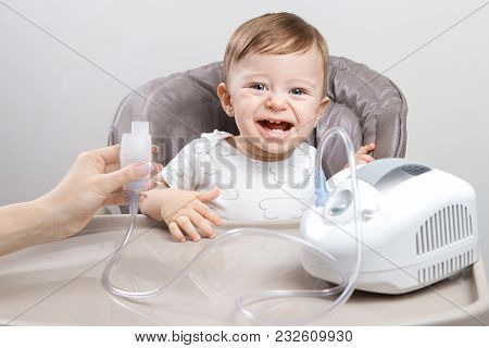 Mother using nebulizer for cute little baby boy sitting on the high chair. Health care concept poster