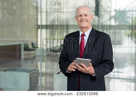 Closeup Portrait Of Smiling Senior Business Man Looking At Camera And Using Tablet Computer In Offic