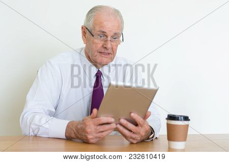 Closeup Portrait Of Surprised Senior Business Man Reading News On Tablet Computer At Office Desk. Su