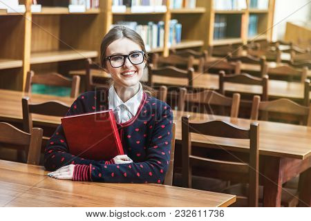 Portrait Of Concentrated Student Wears Glasses Studying In Library, Young Good-looking Woman Reading