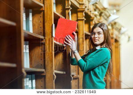 Slender Brunette Wearing Stylish Glasses And Green Sweater Holds Red Book Near Library Bookshelves