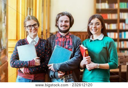 Group Of Students Holding Books In The Library, Indoor Shot In College