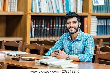 Bearded Awesome Man Using Phone In The Library At The Table Full Og Books