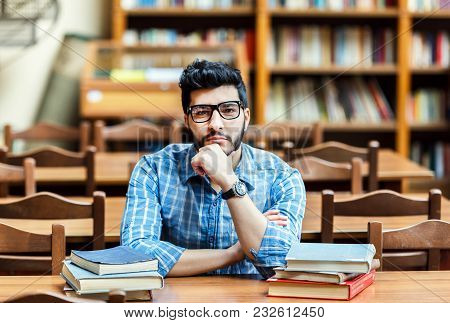 Portrait Of Bearded Student Wears Glassses Thinking At The Table With Books In The Library Reading H