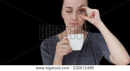 Hot Drink A Sleeping Girl Holding A Cup Of Tea Or Coffee On A Black Background.
