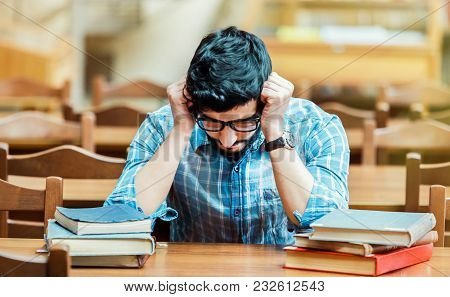 Portrait Of Tired Bearded Student Wears Glassses Thinking At The Table With Books In The Library Rea